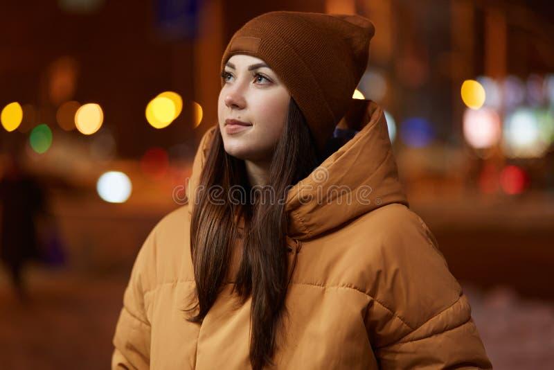 Le tir extérieur de la jeune femme réfléchie utilise le chapeau élégant et la veste brune, a l'expression du visage songeuse, app photos stock