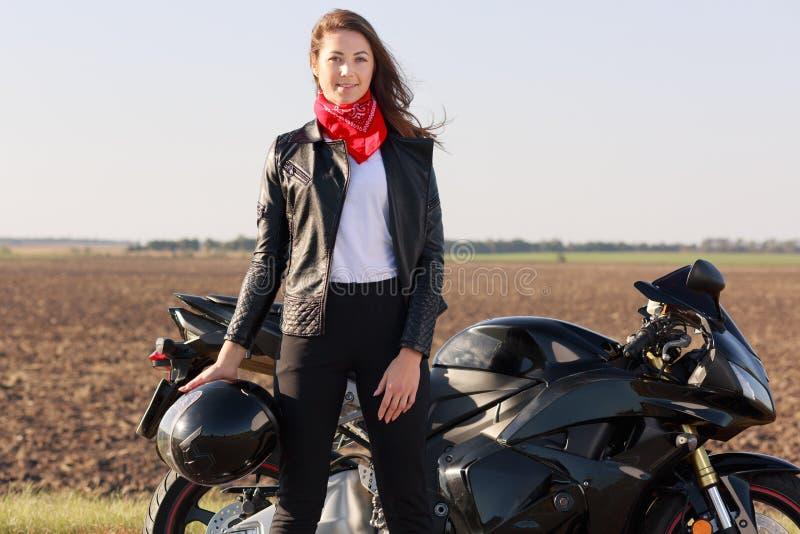 Le tir extérieur du conducteur attrayant de femme avec des supports de cheveux foncés près de motobike rapide noir, tient le casq images stock