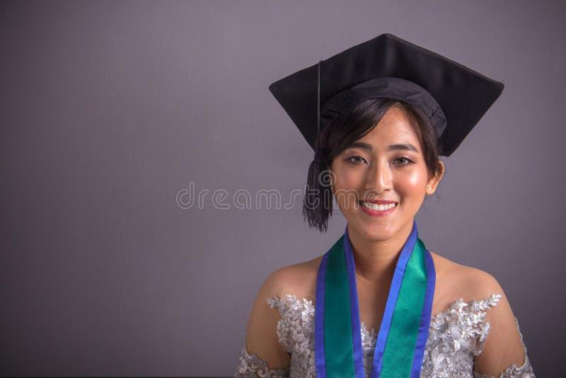 Le tir haut étroit de la graduation asiatique studen au-dessus de gris images stock
