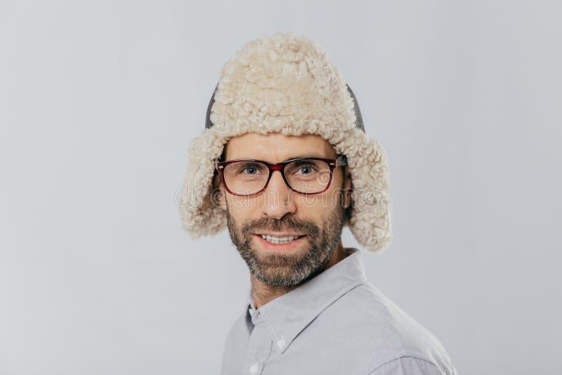 Le tir haut étroit du mâle attirant avec la chaume, porte des lunettes et le chapeau de fourrure, se prépare à l'hiver, a les mod photos libres de droits