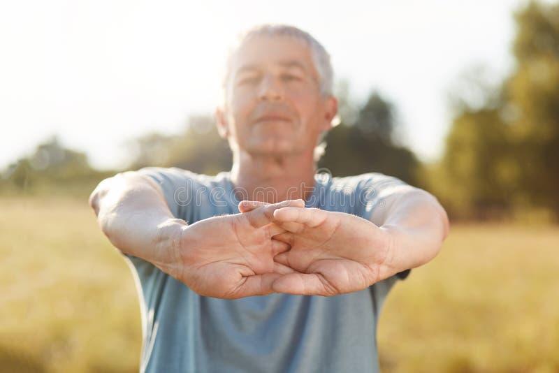 Le tir horizontal du mâle mûr actif beau étire des mains, fait l'exercice physique extérieur, se sent frais et sûr, a l'acte image stock