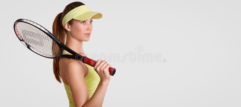 Le tir latéral de la femme réfléchie a la peau propre saine, garde la raquette sur l'épaule, utilise le chapeau de tennis, pense  photo libre de droits