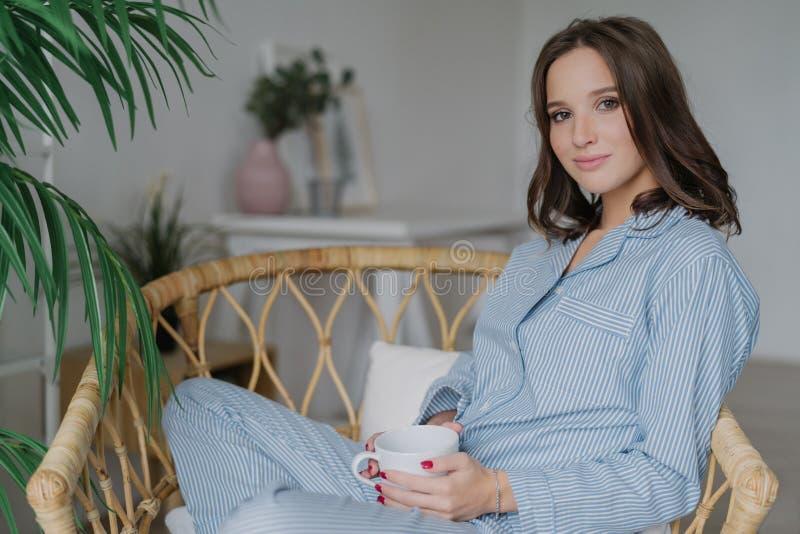 Le tir latéral de la jolie femme repose les jambes croisées dans la chaise en osier, habillée en pyjamas, boissons café chaud et  photos stock