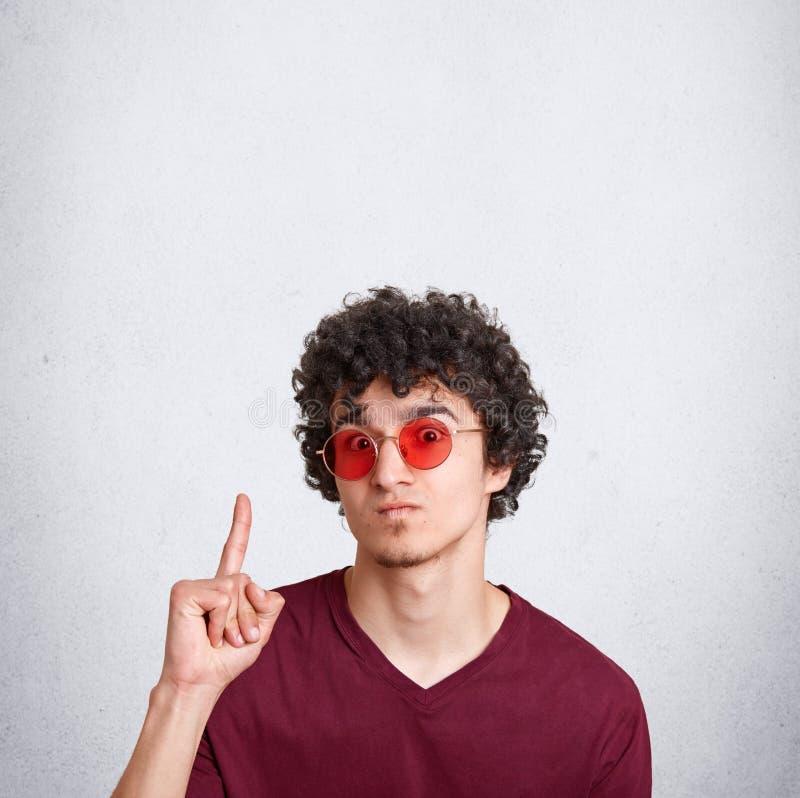 Le tir vertical du type à la mode sérieux de hippie indique avec le doigt antérieur à l'espace vide de copie, montre l'endroit po image stock