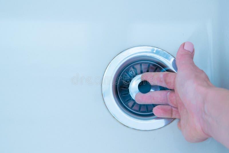 Le tirate della mano della donna chiudono il cappuccio del foro di drenaggio del lavandino per vuotare l'acqua fotografia stock