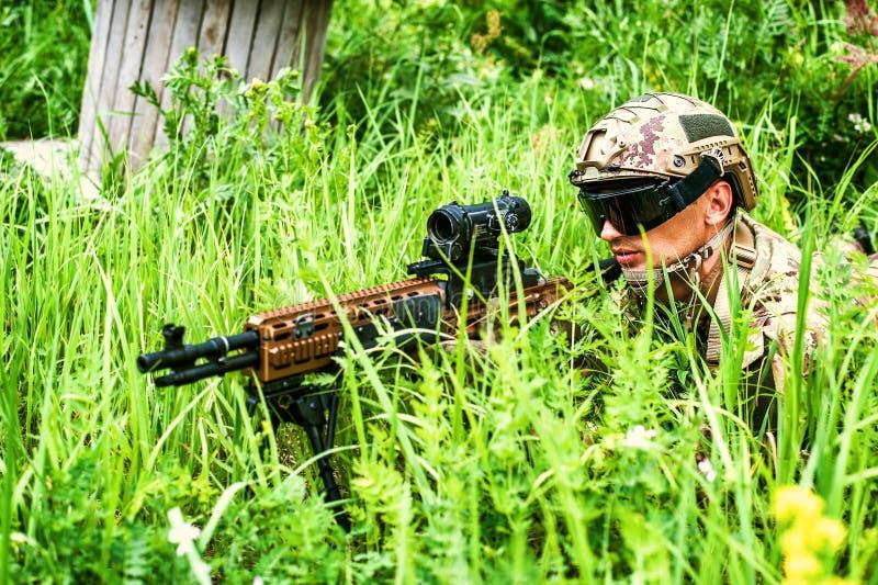 Le tireur isolé de militaire avec l'arme automatique avec une vue télescopique se situe dans l'herbe dans la forêt photographie stock libre de droits