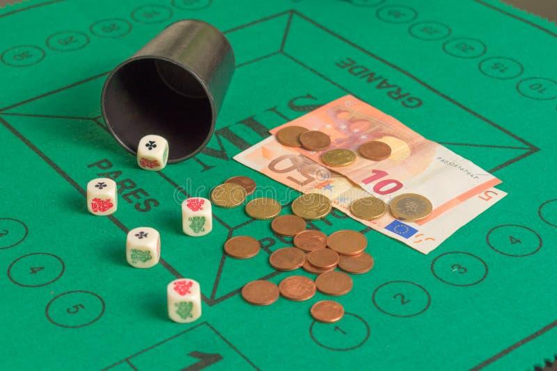 Le tisonnier cinq découpe des ases, des rois, des billets de banque, des pièces de monnaie et du becher dessus photo stock
