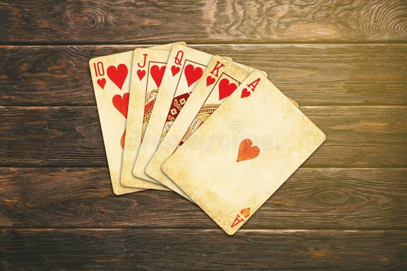 Le tisonnier de quinte royale de coeurs utilisé par vintage carde le dessus de table en bois photo stock