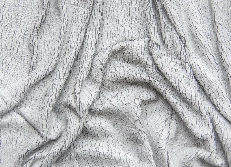 Le tissu en gros plan drapered par cuir âgé criqué a ridé le fond gris photographie stock