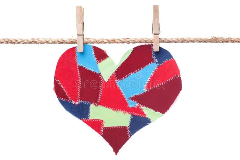 Le tissu ferraille le coeur s'arrêtant sur la corde à linge photo libre de droits