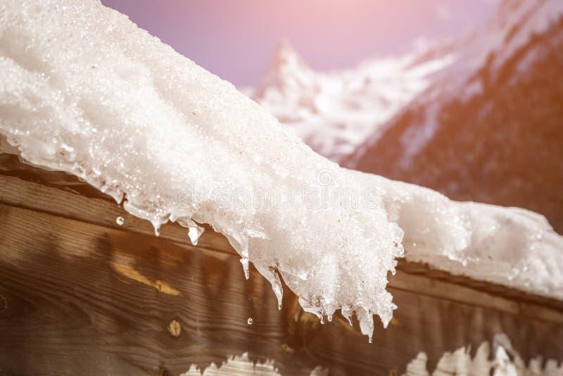 Le toit de la maison est couvert de couche épaisse de neige et de glaçons sur le fond des montagnes couronnées de neige et du sol image stock
