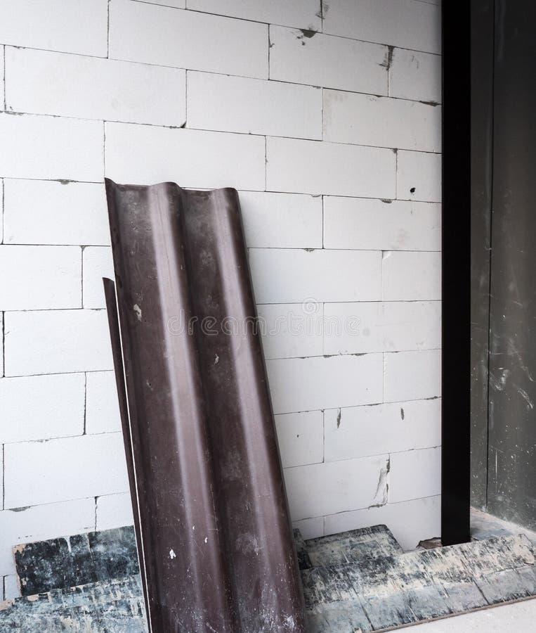 Le toit de tuile foncé s'étend sur le mur de briques photographie stock