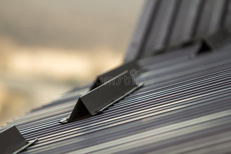Le toit en métal d'une fin de maison avec la neige garde la sécurité photographie stock libre de droits