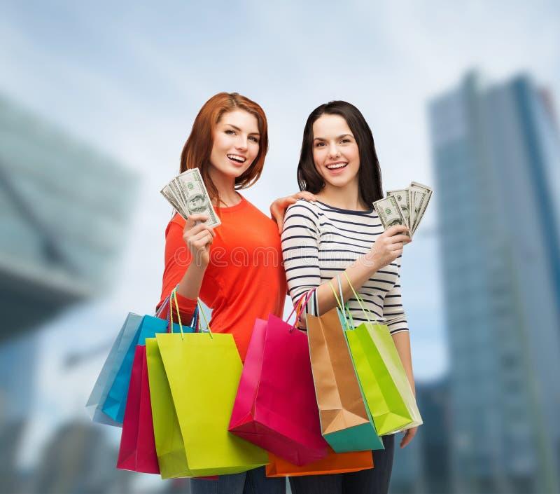 Le tonårs- flickor med shoppingpåsar och pengar arkivfoto