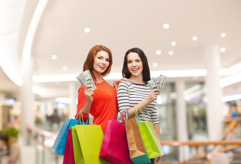 Le tonårs- flickor med shoppingpåsar och pengar arkivbild