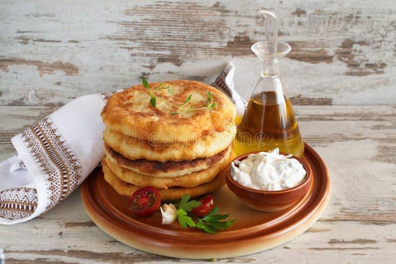 Le tortiglii fritte della patata sono servito con la salsa e gli ortaggi freschi del yogurt immagini stock