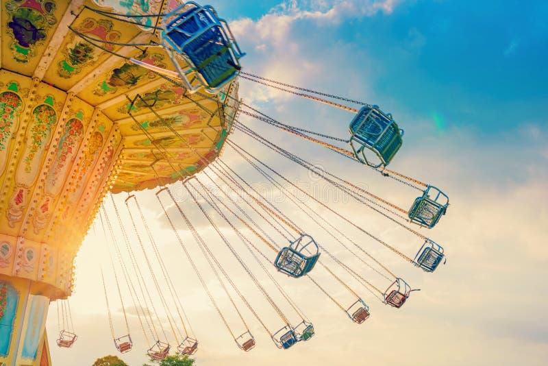 Le tour de carrousel tourne rapidement dans le ciel au coucher du soleil - un carou de oscillation image libre de droits