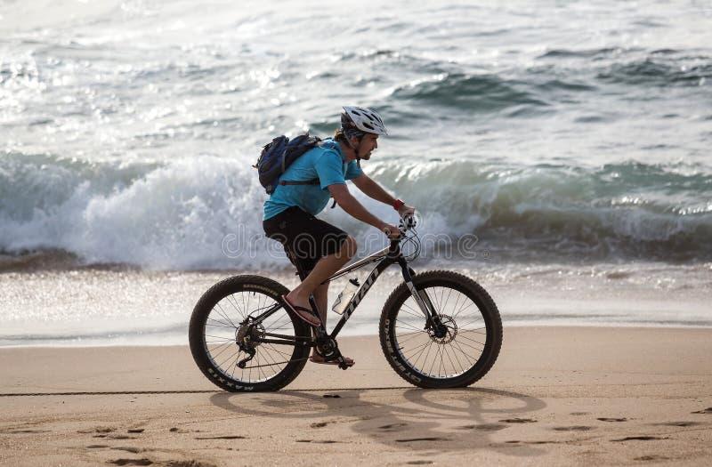 Le tour de vélo à travailler le long de la plage photos libres de droits