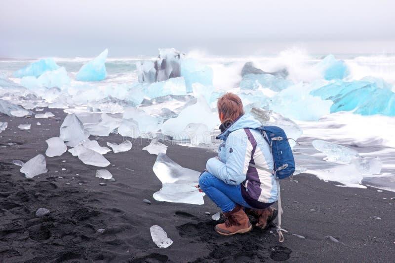 Le touriste à la glace bascule sur la plage noire de sable en Islande photos stock