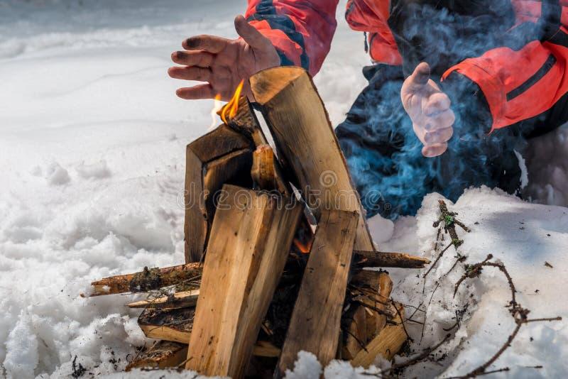 le touriste établit un feu dans la forêt d'hiver photo libre de droits
