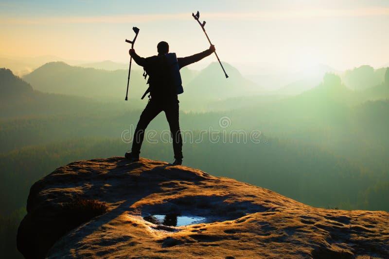Le touriste avec la béquille de médecine au-dessus de la tête a réalisé la crête de montagne Randonneur avec la jambe cassée dans photos libres de droits