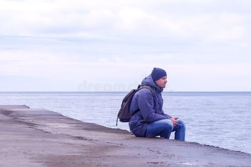 Le touriste d'homme s'assied sur le vieux bord de mer et regards de mer en mer en hiver avec le téléphone photographie stock