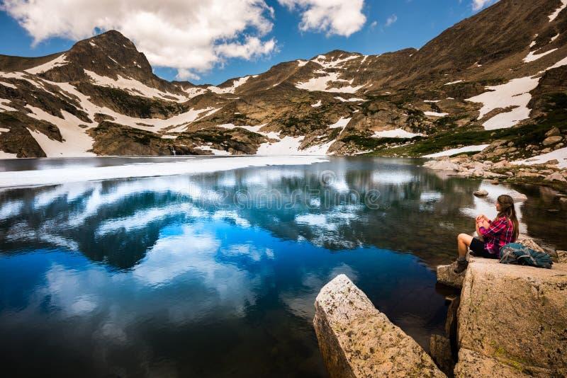 Le touriste dans la fille de randonneur du Colorado se repose au lac bleu image libre de droits