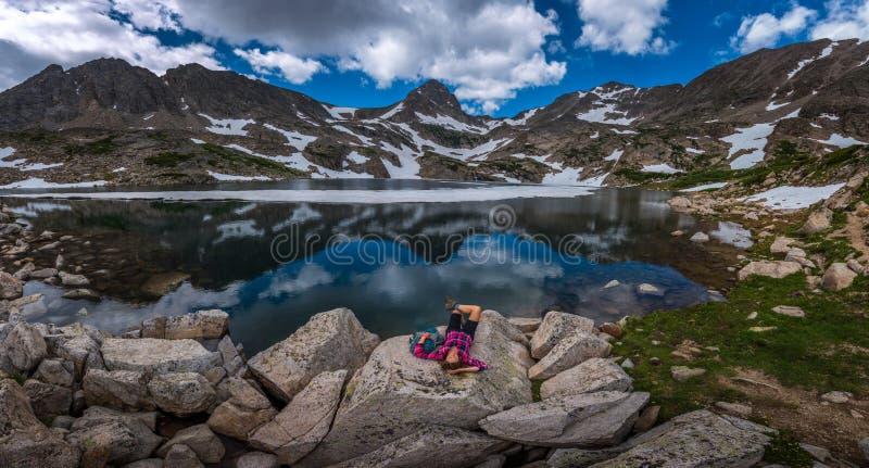 Le touriste dans la fille de randonneur du Colorado se repose au lac bleu photographie stock
