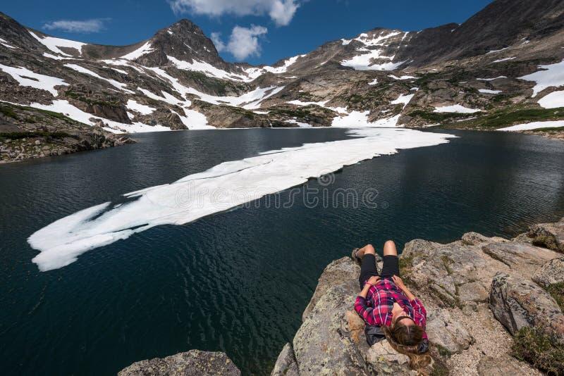 Le touriste dans la fille de randonneur du Colorado se repose au lac bleu photos libres de droits