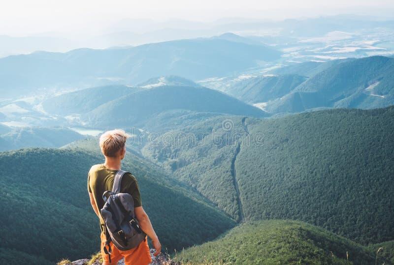 Le touriste de jeune homme se tient sur le dessus de la colline et apprécie avec l'infi images libres de droits