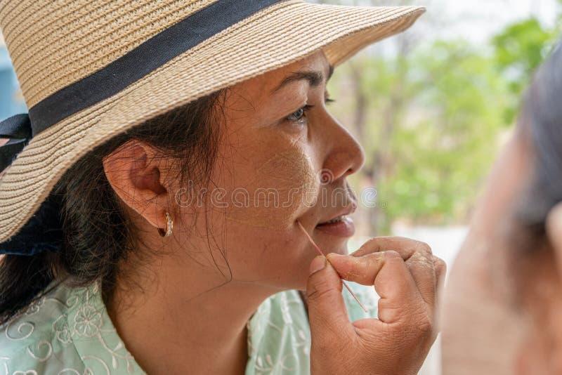 Le touriste féminin asiatique dans Myanmar ont l'application dans le modèle de feuille sur ses joues avec la poudre de Thanaka images libres de droits