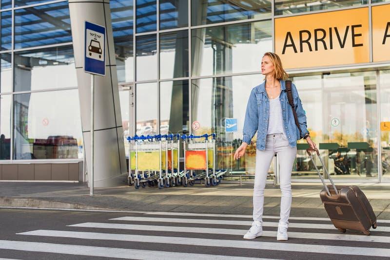Le touriste féminin attend le transport photo stock