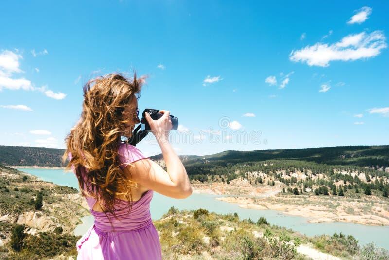 Le touriste féminin aux cheveux longs dans une robe rose avec une caméra se tient dans les montagnes photos libres de droits