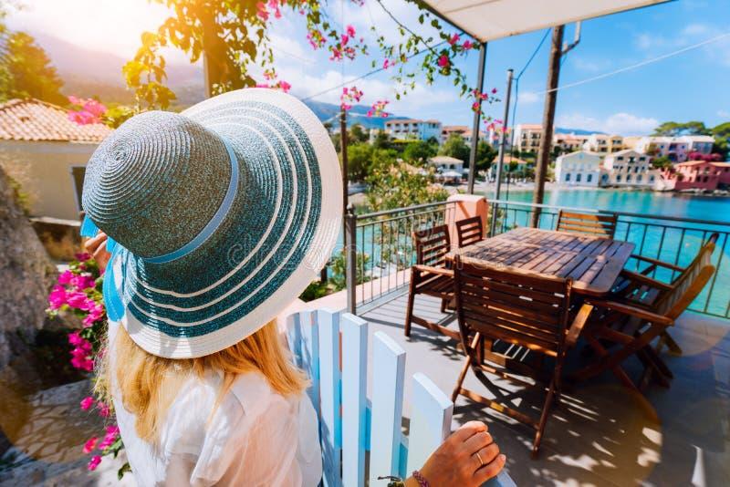 Le touriste féminin dans le chapeau de soleil bleu dans le village d'Assos devant la turquoise admirative de porte confortable de photos stock