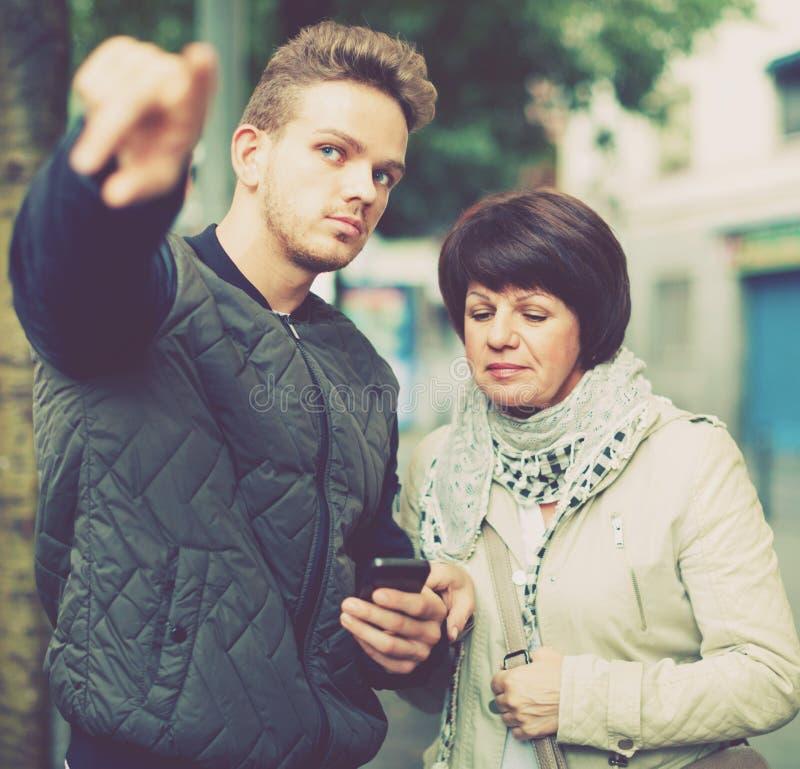 Le touriste féminin demande des directions des gens du pays image libre de droits