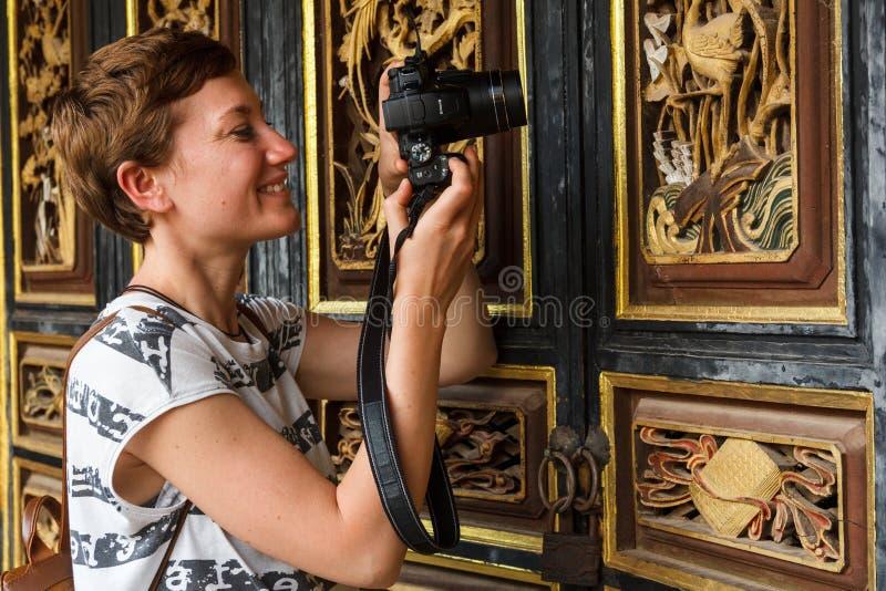 Le touriste féminin en Chine prend la photo du détail ornemental photo stock