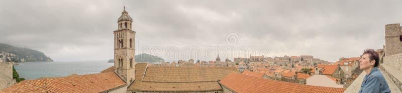 Le touriste féminin regarde au-dessus de Dubrovnik des murs de ville photographie stock libre de droits