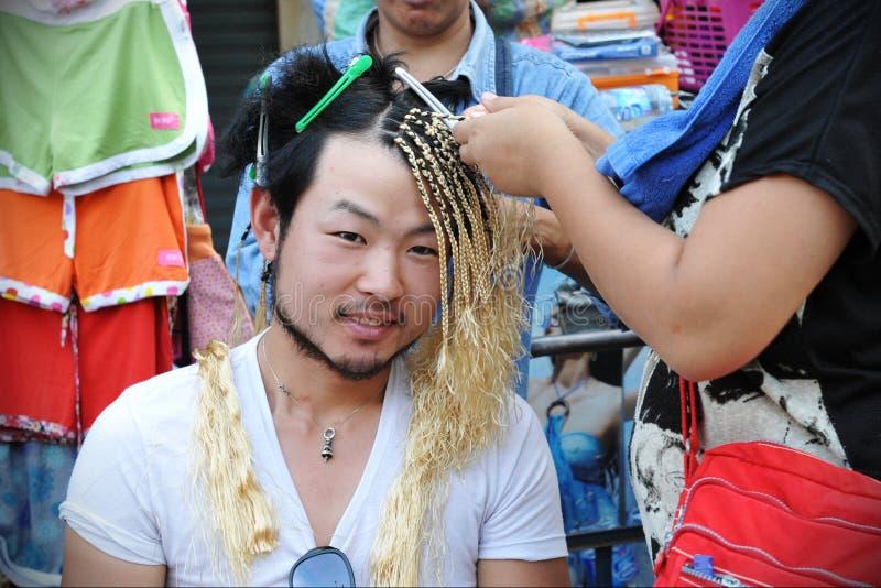 Le touriste fait tresser des cheveux photo stock