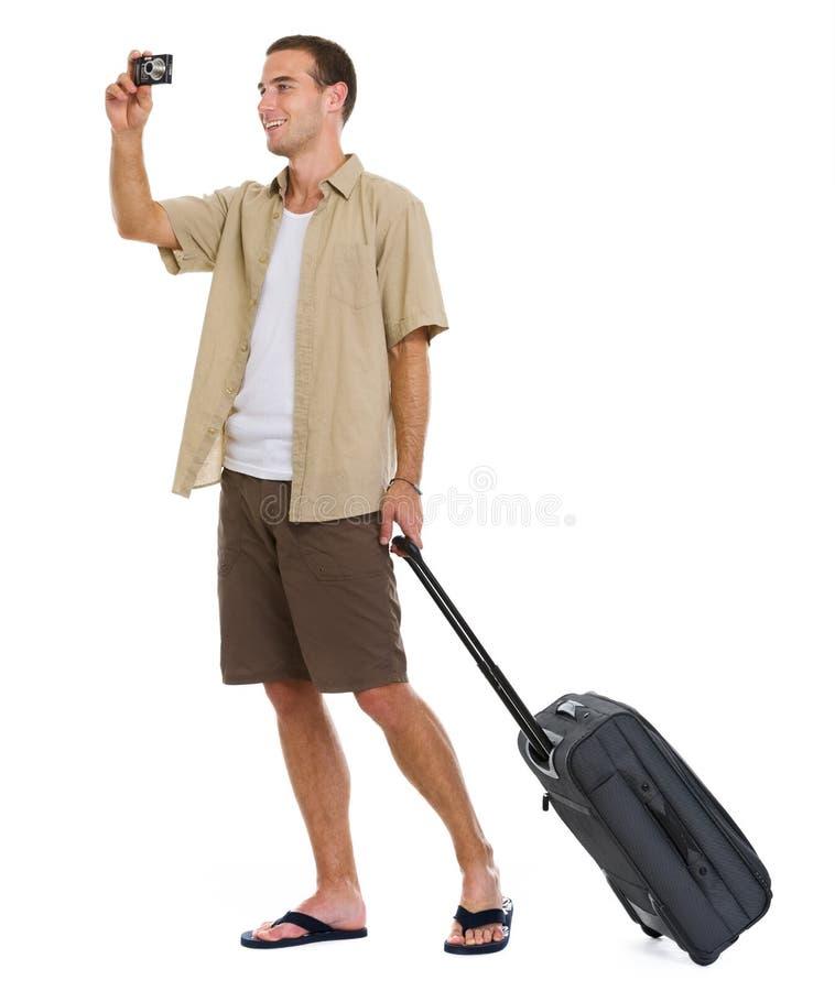 Le touriste heureux avec des roues mettent en sac effectuer la photo images libres de droits