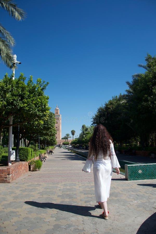 Le touriste occidental marche à la mosquée de Koutoubia, Marrakech image libre de droits