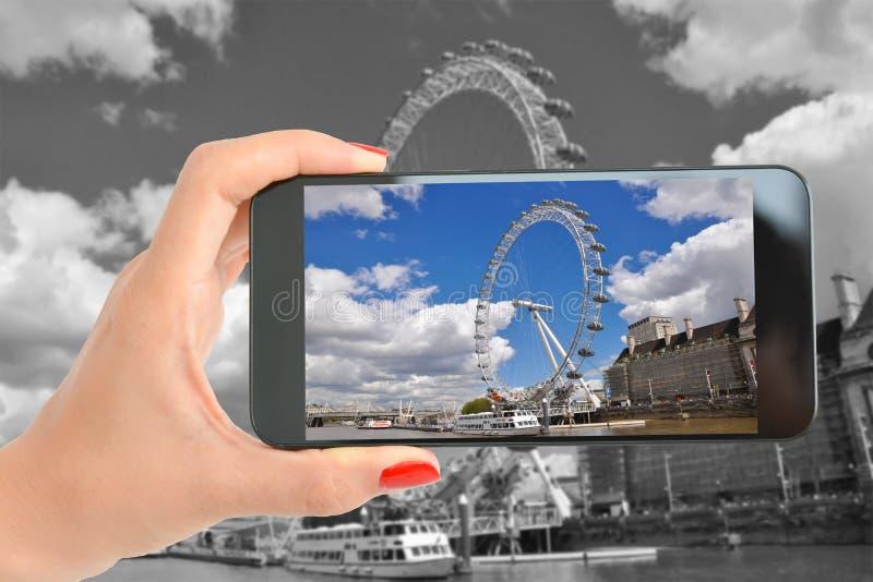 Le touriste prenant une photographie de roue célèbre de carrousel a appelé l'oeil de Londres image stock