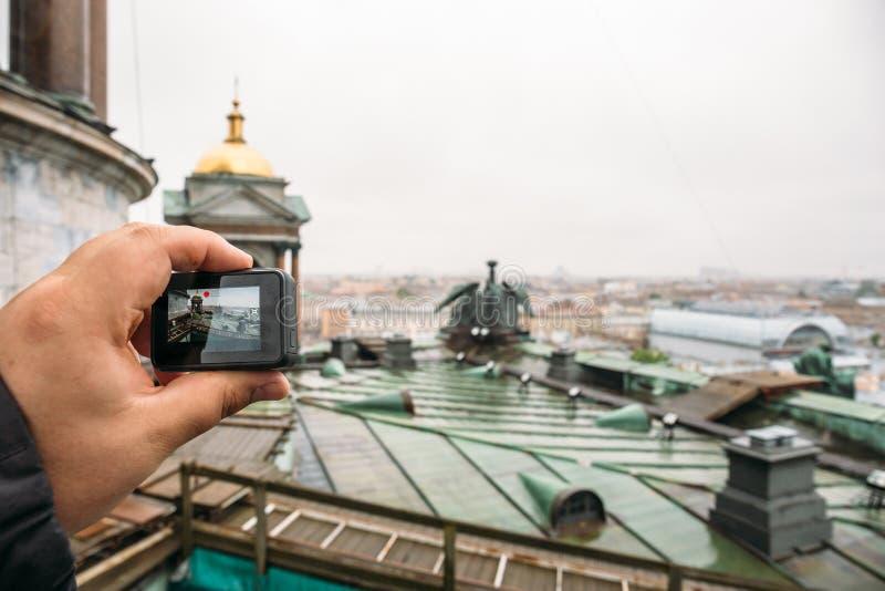 Le touriste tire la vidéo sur le toit d'appareil-photo d'action de la cathédrale du ` s de St Isaac à St Petersburg images stock