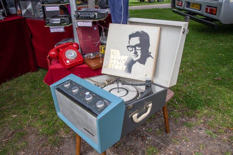 Le tourne-disque de cru qui a le couvercle ouvert et une copie de disque de Buddy Holly Story se penche contre le couvercle photographie stock