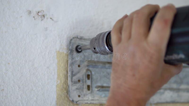 Le tournevis électrique serrent des vis sur le climatiseur d'intérieur images libres de droits