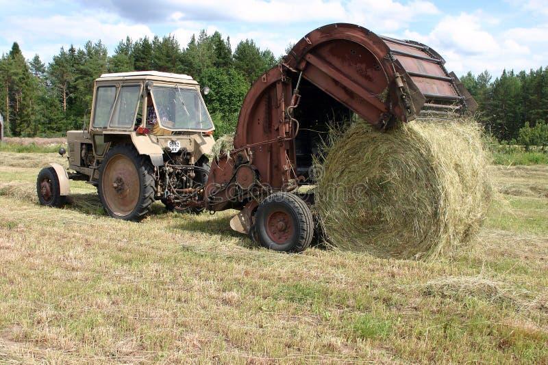 Le tracteur avec la presse ronde rassemble le foin à la prairie de fauche photo libre de droits
