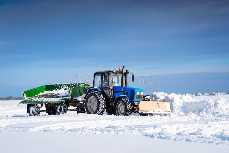 Le tracteur bleu avec une remorque nettoie la neige avec une pelle photographie stock