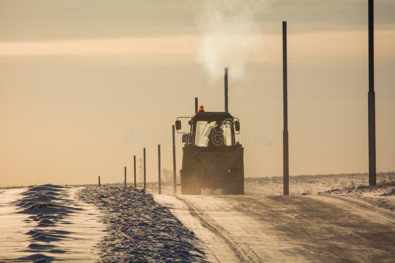 Le tracteur conduit le long de la route russe d'hiver image stock