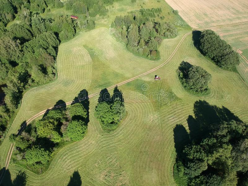 Le tracteur a coupé la fenaison d'herbe sur le champ de terres cultivables, vue aérienne photos stock