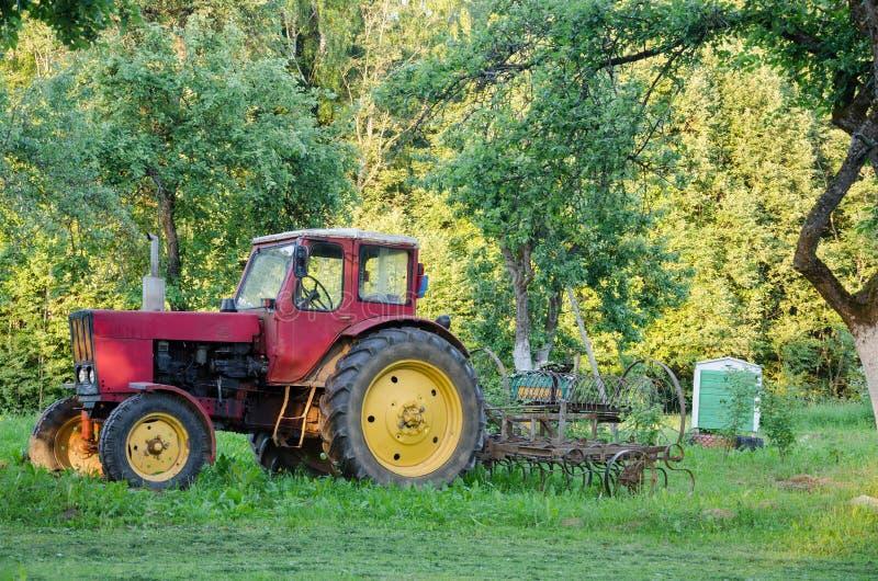 Le tracteur de ferme avec le jaune roule le harow dans le jardin photos stock