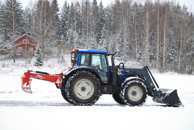 Le tracteur de Valtra enlève la neige avec l'entrave de seau et de route images stock